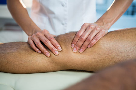 recuperation: Mid section of physiotherapist giving leg massage to a patient in clinic