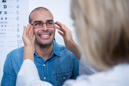 ophthalmology: Female optometrist prescribing spectacles to patient in ophthalmology clinic Stock Photo