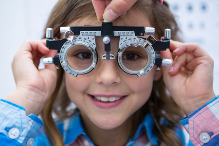 ophthalmology: Young girl wearing trial fame in ophthalmology clinic Stock Photo