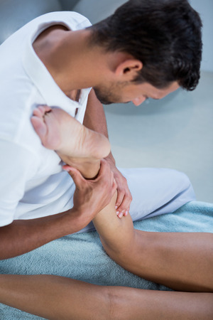 Physiotherapist giving leg massage to a woman in clinic Stock Photo