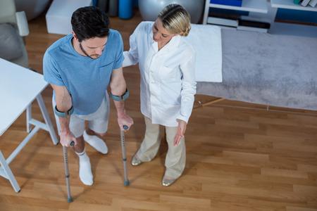 Fisioterapista che aiuta il paziente a camminare con le stampelle in clinica Archivio Fotografico - 61670585