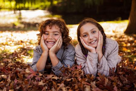 siblings: Portrait of happy siblings lying on autumn leaves at park
