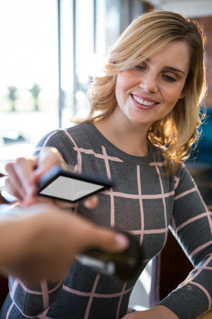 cafeteria: Woman making payment through smartphone in cafeteria Stock Photo