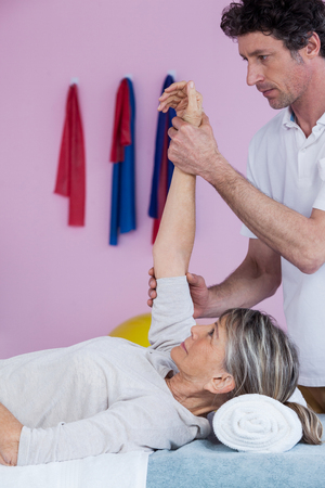 recuperation: Physiotherapist massaging a senior womans hand in clinic