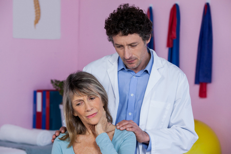 senior man on a neck pain: Physiotherapist massaging a senior womans shoulder in clinic