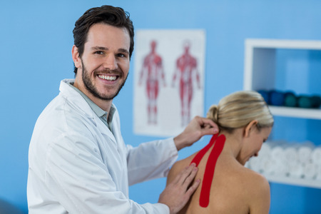Physiotherapist sticking tape on female patient in clinic Stock Photo - 61664711
