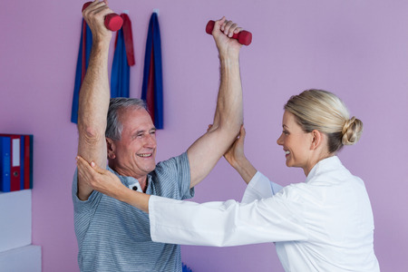 Physiotherapist assisting senior man to lift dumbbellin clinic Stock Photo