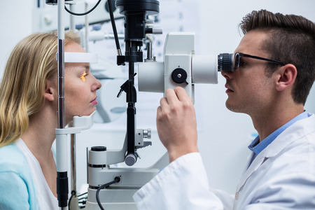 slit: Attentive optometrist examining female patient on slit lamp in ophthalmology clinic Stock Photo