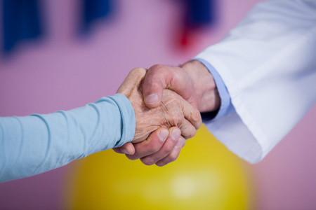 Physiotherapist shaking hands with patient in clinic