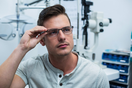 ophthalmology: Close-up of handsome patient trying spectacles in ophthalmology clinic