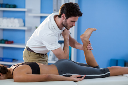 Male physiotherapist giving hip massage to female patient in clinic Stock Photo