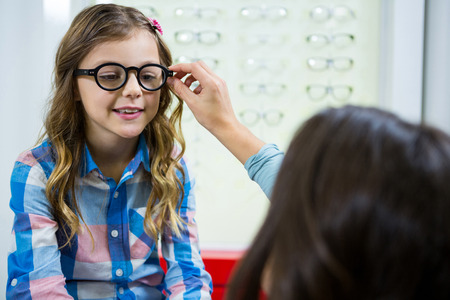 Mother prescribing spectacles to her daughter in optical store Reklamní fotografie