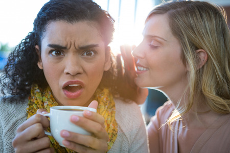 Woman whispering a secret into her friends ear while having coffee in coffee shop
