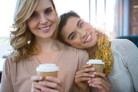 Portrait of smiling female friends sitting together and having coffee in cafeteria Stock Photo