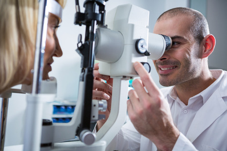optometrist: Optometrist examining female patient on slit lamp in ophthalmology clinic