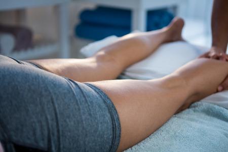 leg massage: Physiotherapist giving leg massage to a woman in clinic Stock Photo