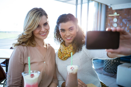 taking refreshment: Smiling female friends taking a selfie on mobile phone in cafeteria