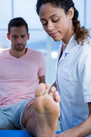 leg massage: Physiotherapist giving leg massage to a man in clinic