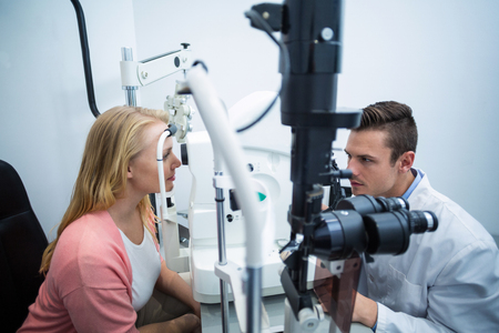 ophthalmology: Optometrist examining female patient on coreometry in ophthalmology clinic Stock Photo