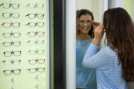 wearing spectacles: Female customer wearing spectacles and checking in mirror at optical store
