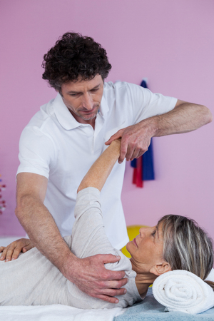 recuperation: Physiotherapist massaging a senior womans shoulder in clinic