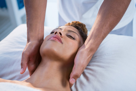 neck massage: Woman receiving neck massage from physiotherapist in clinic Stock Photo