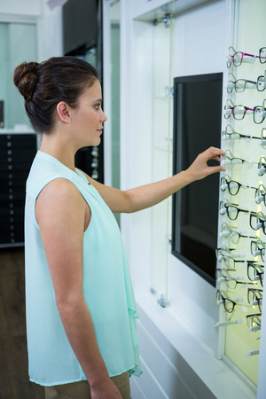 selecting: Beautiful female customer selecting spectacles in optical store
