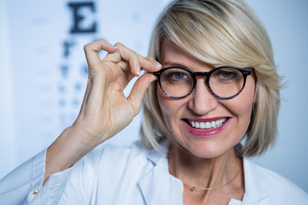 optometrist: Portrait of smiling optometrist wearing spectacles in ophthalmology clinic
