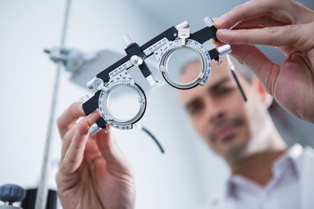 trial indoor: Close-up of optometrist holding messbrille in ophthalmology clinic