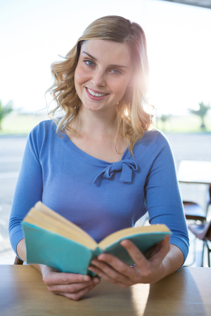 novel: Portrait of smiling woman reading a book in the coffee shop