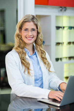 ophthalmology: Beautiful optometrist using laptop in ophthalmology clinic Stock Photo