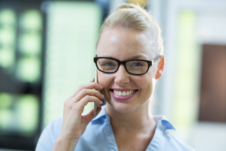 Portrait of smiling female customer talking on mobile phone in optical store Stock Photo