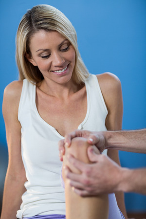 recuperation: Male physiotherapist giving knee massage to female patient in clinic Stock Photo