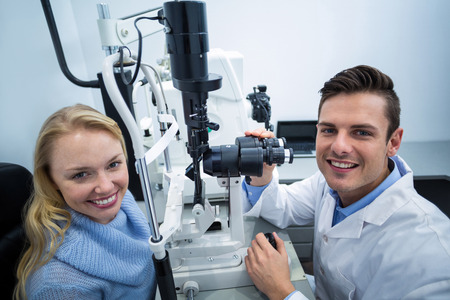 slit: Portrait of optometrist examining female patient on slit lamp in ophthalmology clinic Stock Photo