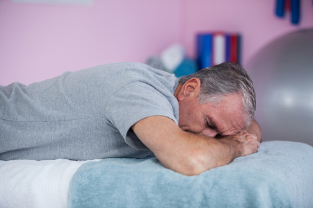 Senior man lying on a massage bed in clinic