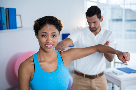 examining: Physiotherapist examining womans shoulder in clinic