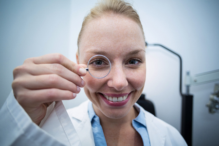 Close-up of female optometrist looking through magnifying glass in ophthalmology clinic