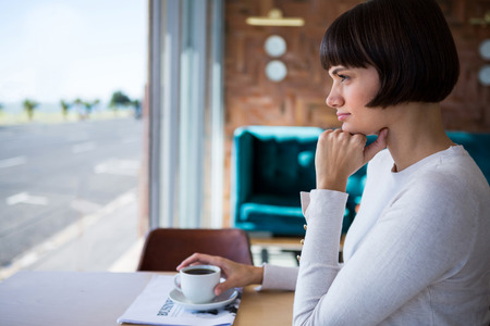 cafeteria: Thoughtful woman sitting in cafeteria Stock Photo