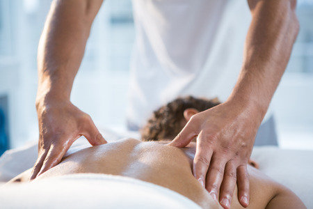 Woman receiving back massage from physiotherapist in clinic Фото со стока - 61687440