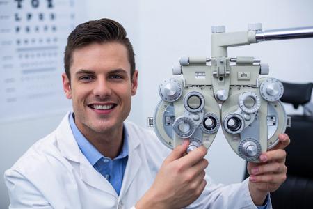 optometrist: Smiling optometrist adjusting phoropter in ophthalmology clinic