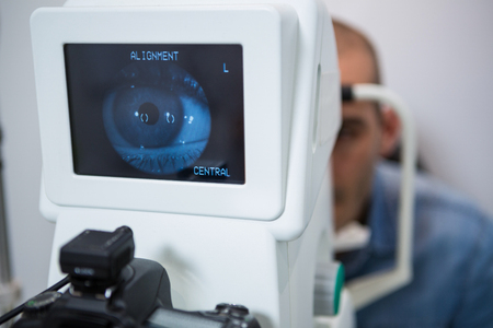 ophthalmology: Man looking at eye test machine in ophthalmology clinic