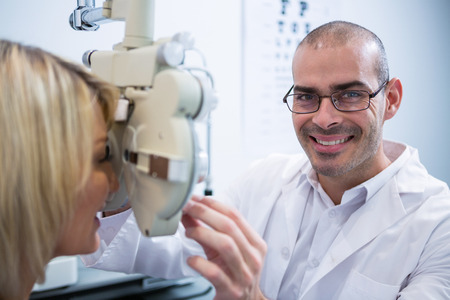 ophthalmology: Smiling optometrist examining female patient on phoropter in ophthalmology clinic