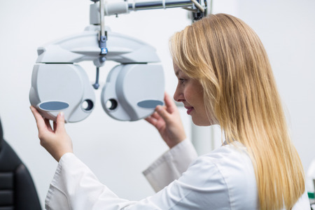 attentive: Attentive female optometrist adjusting phoropter in ophthalmology clinic