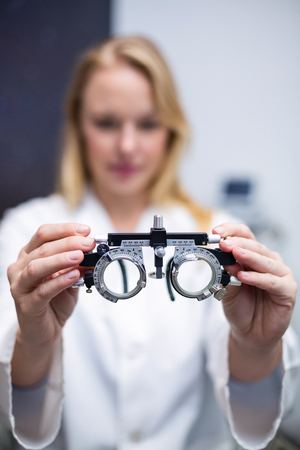 trial indoor: Close-up of female optometrist holding messbrille in ophthalmology clinic Stock Photo