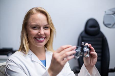 diopter: Portrait of smiling female optometrist holding messbrille in ophthalmology clinic Stock Photo