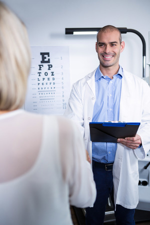 optometrist: Male optometrist talking to female patient in ophthalmology clinic