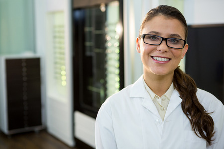 optometrist: Portrait of optometrist in spectacles smiling in optical store Stock Photo