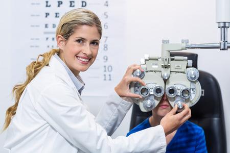 Optometrista femminile che esamina giovane paziente su phoropter nella clinica di oftalmologia Archivio Fotografico - 61668967