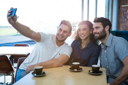 tomando refresco: amigos tomando una autofoto en la tienda de café sonriendo