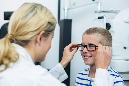 prescribing: Female optometrist prescribing spectacles to young patient in ophthalmology clinic Stock Photo
